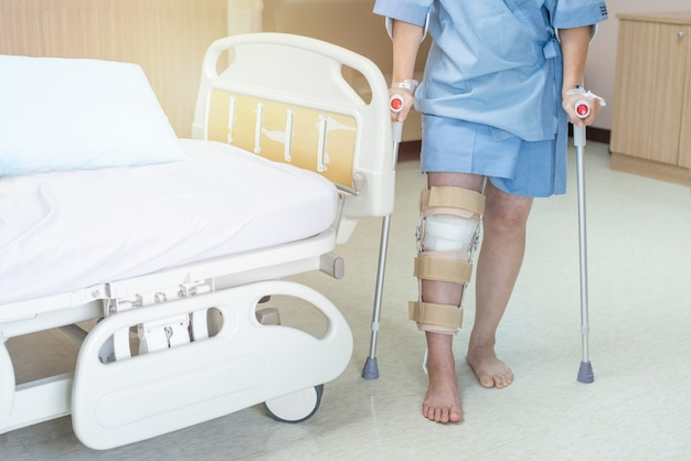 Asian woman patient with knee brace with walking stick in hospital ward after ligament surgery.