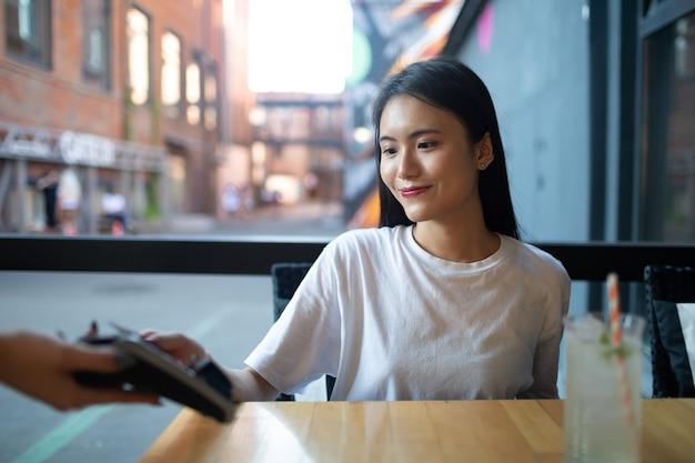 아시아 여성은 야외 카페에서 신용카드 비접촉식 결제 단말기 출납원으로 결제합니다.