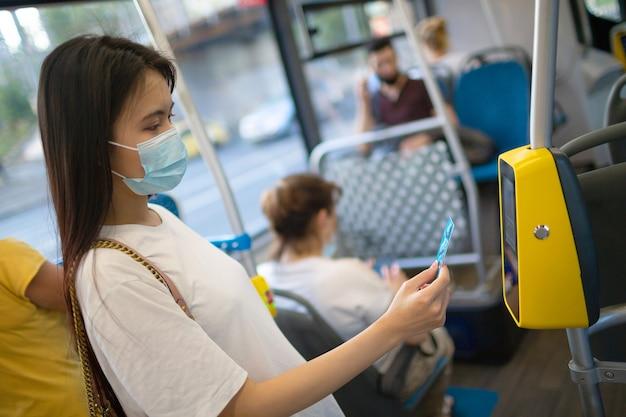 Азиатская женщина бесконтактно платит пластиковой картой за общественный транспорт в автобусе
