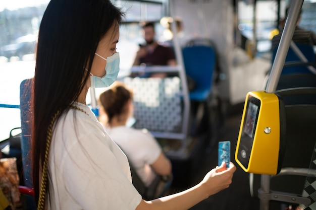 Asian woman paying conctactless with plastic card for the public transport in bus