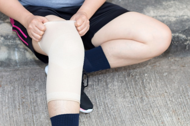 Asian woman people or sport woman wearing the knee support or athlete knee strap