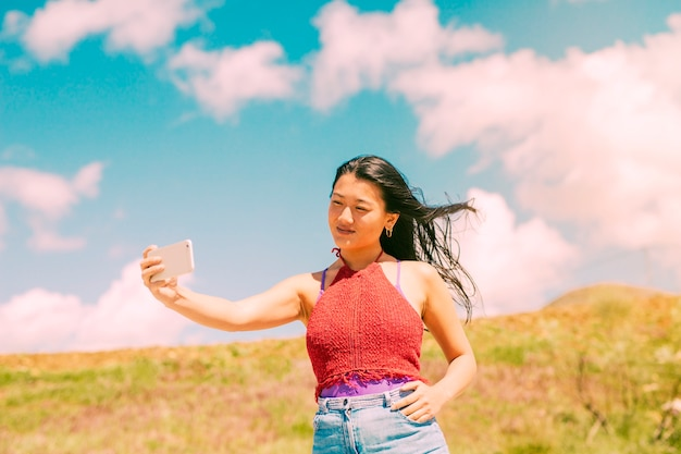 Asian woman photographing in field