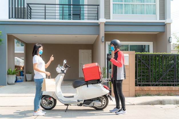 Asian woman pick up delivery food bag from box and thumb up form contactless or contact free from delivery rider with bicycle in front house for social distancing for infection risk. coronavirus concept