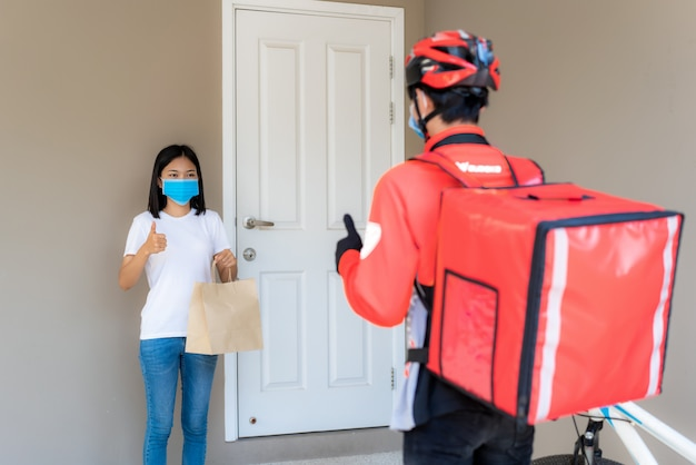 Asian woman pick up delivery food bag from door knob and thumb up form contactless or contact free from delivery rider with bicycle in front house for social distancing for infection risk. coronavirus concept