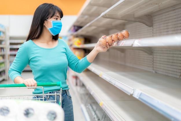 アジアの女性は、covid-19コロナウイルスの恐怖、買い物客のパニック購入、パンデミックの準備をするトイレットペーパーの備蓄の中で、スーパーマーケットの空の棚で最後の卵パックを受け取ります。