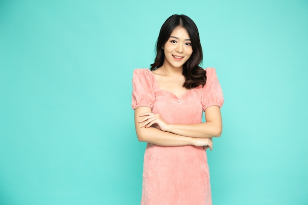 Asian woman in pink dress with arms crossed and smile isolated over green.