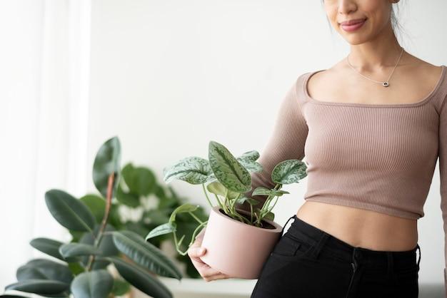 화분에 심은 관엽 식물을 들고 아시아 여자 식물 부모