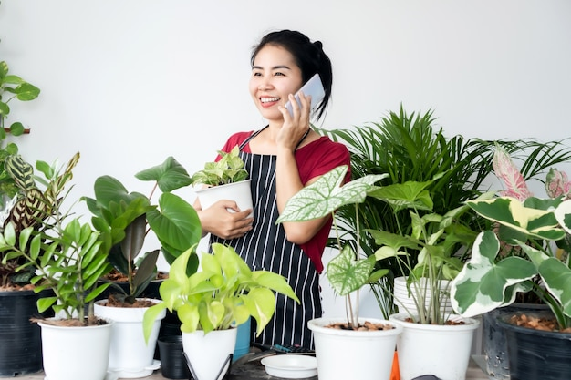 아시아 여성 식물 소유자 상점은 스마트폰으로 식물을 판매하고 고객으로부터 주문을 받고 소규모 비즈니스 개념