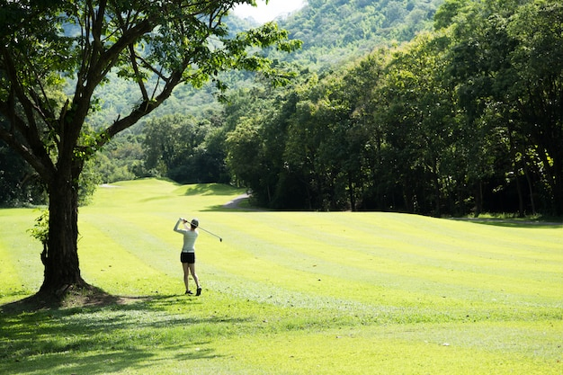 Азиатская женщина играет в гольф на красивом естественном поле для гольфа