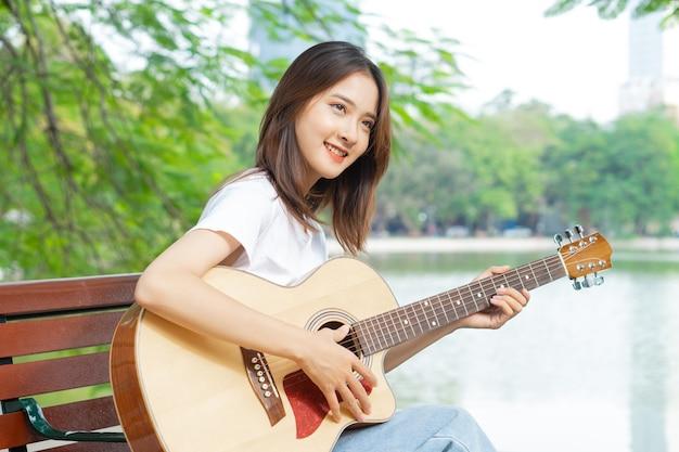 거리에서 기타를 연주하는 아시아 여성