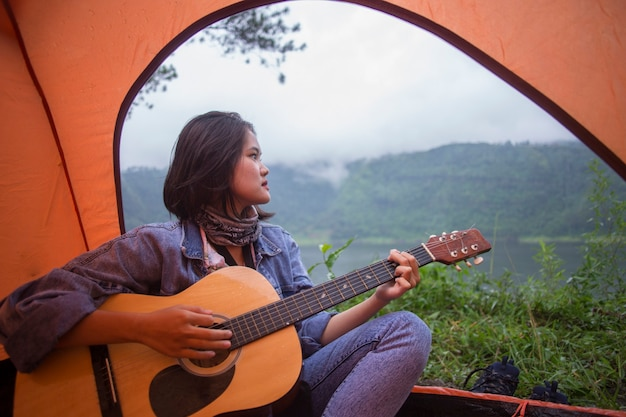 Asian woman playing guitar in a tent, in the morning
