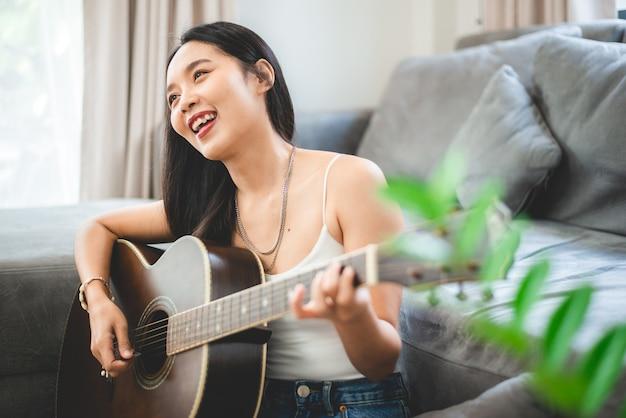 Азиатская женщина играет на гитаре дома, образ жизни молодой гитаристки-музыканта с акустическим художественным инструментом сидит, чтобы играть и петь песню, издающую звук в хобби в комнате дома