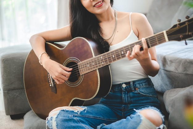 Asian woman playing music by guitar at home, young female guitarist musician lifestyle with acoustic art instrument sitting to play and sing a song making sound in hobby in the house room