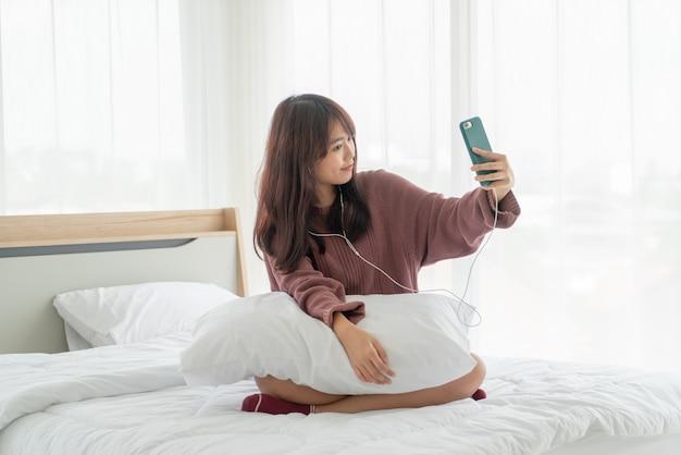 アジアの女性がベッドの上のスマートフォンを再生