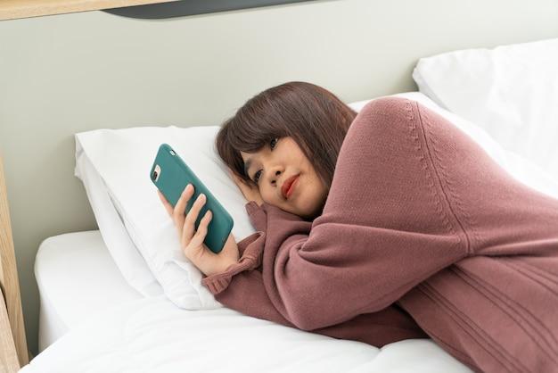 ベッドでスマートフォンを再生するアジアの女性