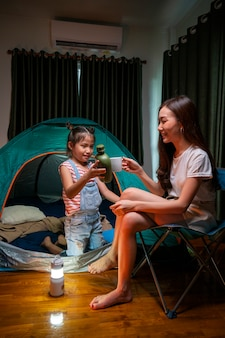 Asian woman playing and staying in tent with her daughter and having fun with camping tent in their bedroom