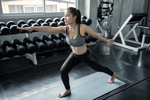 Asian woman playing yoga in the gym.