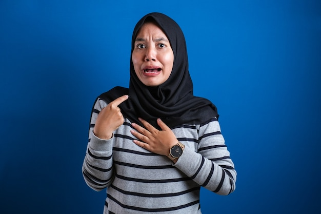 Asian woman pointing herself with unhappy displeased expression as if he confused to be accused and asking who? me?