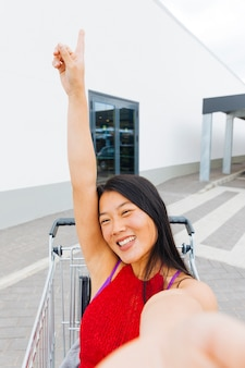 Азиатская женщина позирует и принимая селфи в тележке для покупок