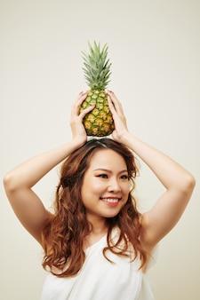アジアの女性がパイナップルでポーズ