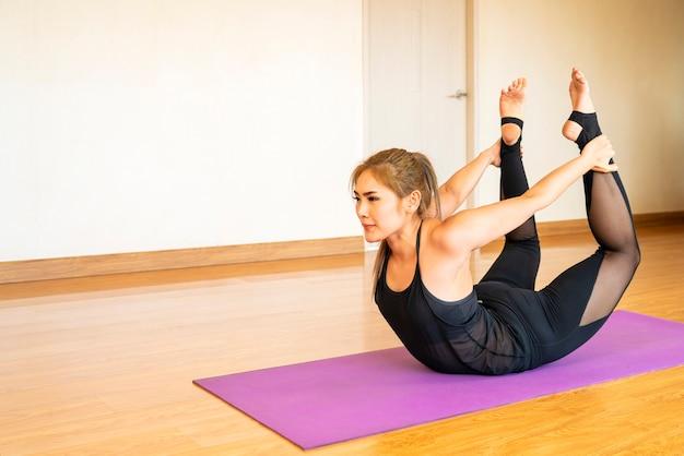 집에서 그녀의 거실에서 요가 매트에 아시아 여자 연습 요가 운동 운동. 건강한 생활 습관, 새로운 일반 또는 가정 격리 개념