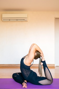 Asian woman practice yoga workout exercise on yoga mat in her living room at home. healthy lifestyle, new normal or home quarantine concept