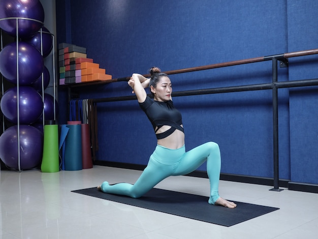 Asian woman practicing advanced yoga fitness stretching training