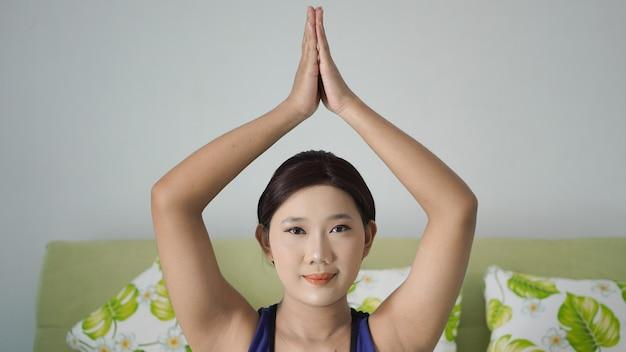 手上げ運動をしている家でヨガを練習しているアジアの女性