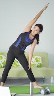 Азиатская женщина занимается йогой дома, разогревая мышцы боковым движением