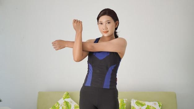 Азиатская женщина занимается йогой дома, разогревая жест рукой