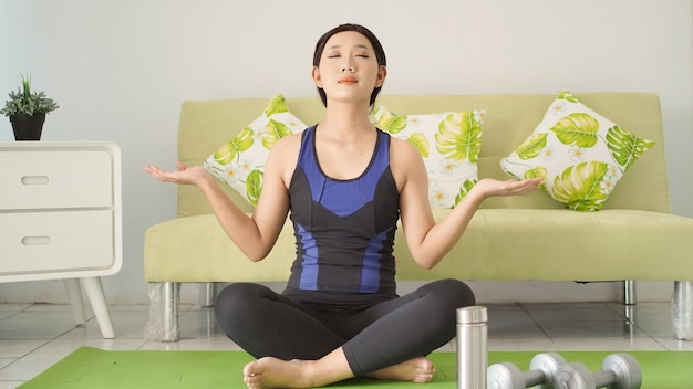 集中力を持って自宅でヨガを練習しているアジアの女性