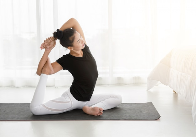 Asian woman practicing yoga, doing mermaid exercise or eka pada rajakapotasana pose in the bedroom