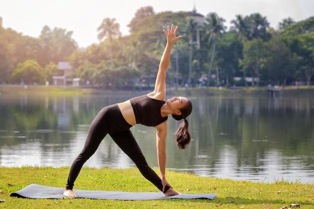 Asian woman practicing yoga doing utthita trikonasana exercise extended triangle pose