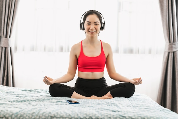 Covid19の発生時に寝室のベッドで自宅からヨガを練習しているアジアの女性