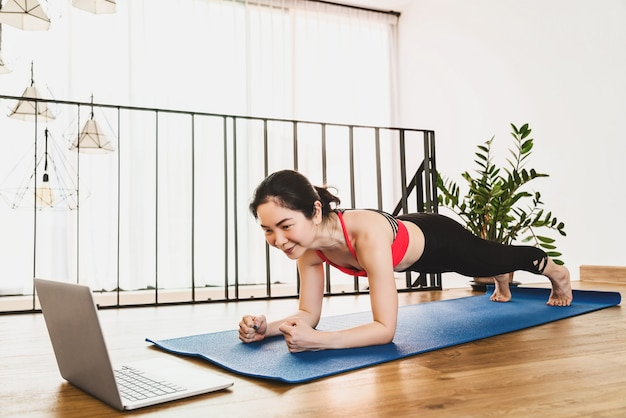 Covid19の発生と封鎖時にラップトップで自宅からヨガを練習しているアジアの女性