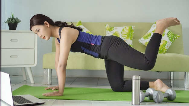 Asian woman practicing yoga at home doing leg lifts up