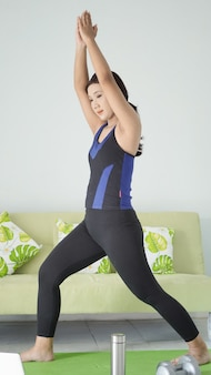 Asian woman practicing yoga at home doing muscle warm up