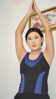 Asian woman practicing yoga at home doing warm up hand movement