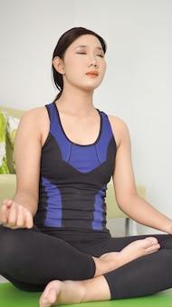 自宅で集中的にヨガを練習しているアジアの女性