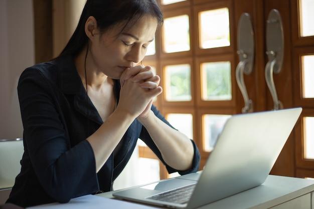 노트북, 책, 노트북으로 믿음으로기도하는 아시아 여자. 가정 개념에서 온라인 교회입니다.
