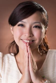 祈るアジアの女性、スタジオの茶色の背景にクローズアップの肖像画。