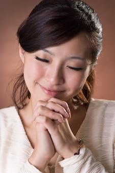 Asian woman praying, closeup portrait on studio brown background.