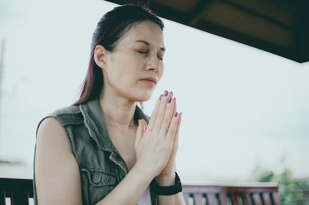 屋外で朝を祈るアジアの女性、信仰、精神性、宗教のための祈りの概念に手を組んで、教会はオンラインの概念を提供しています。