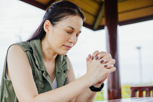 Asian woman praying morning outdoor, hands folded in prayer concept for faith, spirituality and religion, church services online concept.