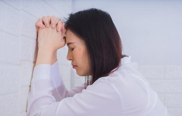 벽에 기도하고 신을 믿는 아시아 여성.