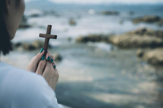 ビーチで木製の十字架と祈りのアジアの女性