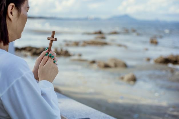 ビーチで木製の十字架で祈るアジアの女性