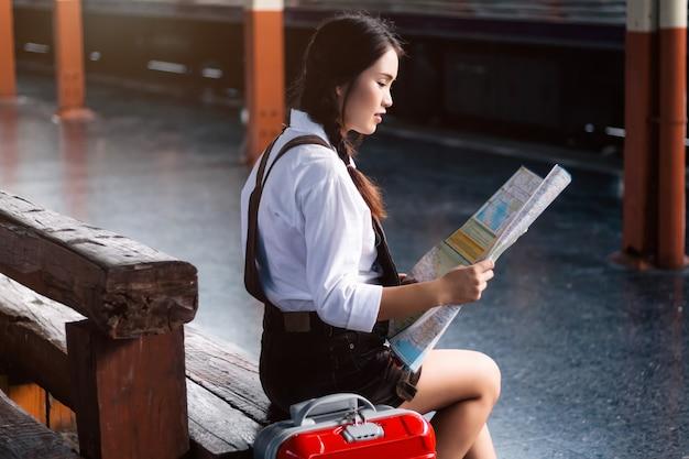アジアの女性妊娠中の鉄道駅旅行で地図を見てください。