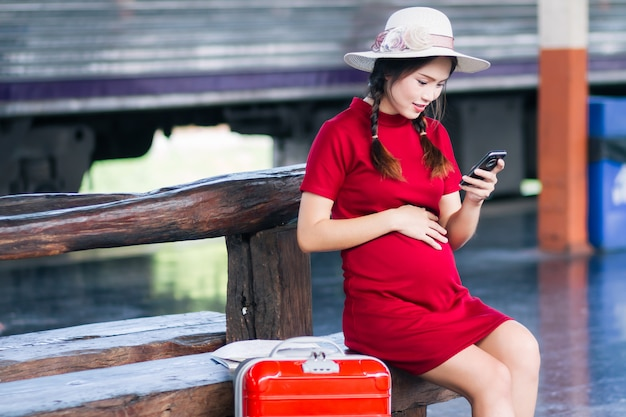 Asian woman pregnant in red dress carrying red luggage and look at the smartphone with a red suitcase
