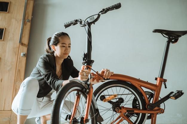 Азиатка готовит складной велосипед из дома к работе